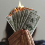 One hundred dollar bills lit on fire