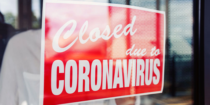 "Man hanging a sign on a restaurant door that says, ""Closed due to Coronavirus"""