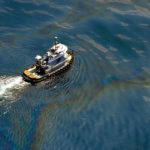 A boat traversing an oil spill in the Gulf of Mexico